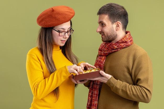 Jonge mooie paar gelukkig man chocolade snoepjes aanbieden aan zijn lachende mooie vriendin in baret vieren valentijnsdag staande over groene achtergrond