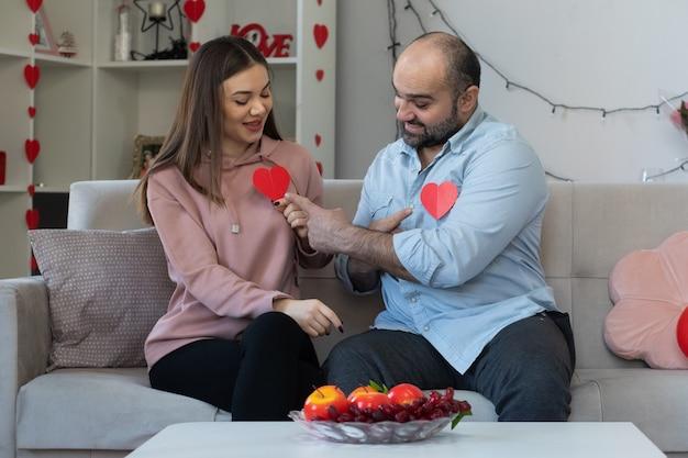 Jonge mooie paar gelukkig man en vrouw met hart gemaakt van karton glimlachend plezier samen vieren saint valentine's day zittend op een bank in lichte woonkamer