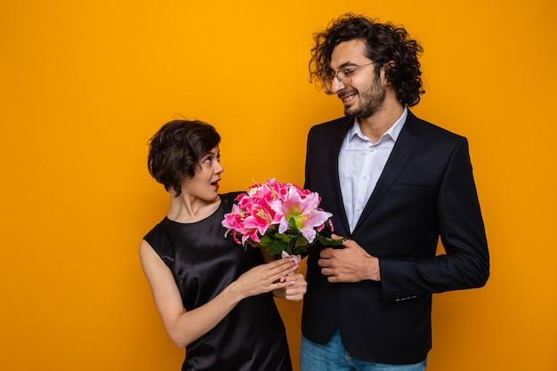 Jonge mooie paar gelukkig man kijken naar zijn verrast vriendin met boeket bloemen glimlachend vrolijk gelukkig verliefd vieren internationale womens dag