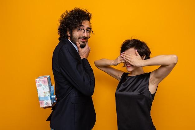 Jonge mooie paar gelukkige en glimlachende man verbergen aanwezig gaan geven aan zijn verbaasde vriendin die ogen bedekken met handen vieren internationale vrouwendag