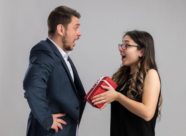 Jonge, mooie paar gelukkige en verraste man die naar zijn lieftallige vriendin kijkt met een cadeau voor hem om valentijnsdag te vieren die over een witte muur staat