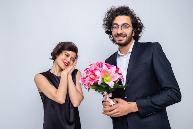 Jonge, mooie paar gelukkige man die een boeket bloemen geeft aan zijn lieftallige vriendin, gelukkig verliefd om valentijn te vieren