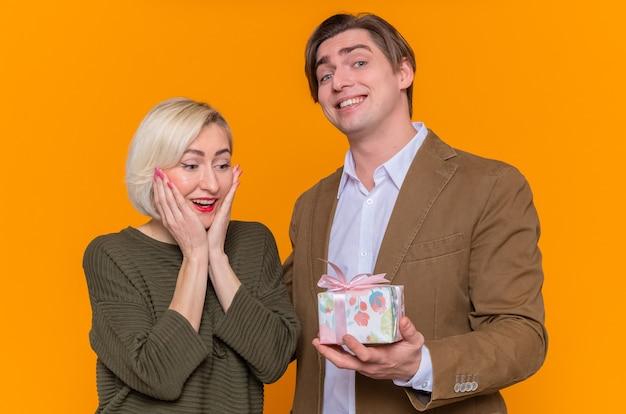Jonge mooie paar gelukkige man die een cadeau geeft aan zijn mooie verraste vriendin