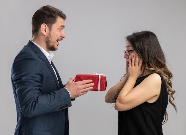 Jonge, mooie paar gelukkige man die een cadeau geeft voor zijn lieftallige vriendin die gelukkig verliefd is en valentijnsdag viert die over een witte muur staat