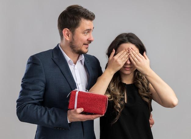Jonge, mooie paar gelukkige man die een cadeau geeft voor zijn lieve vriendin terwijl ze haar ogen bedekt, gelukkig verliefd en valentijnsdag viert