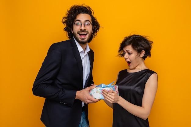 Jonge mooie paar gelukkige man die een cadeautje geeft aan zijn verraste en verbaasde vriendin die internationale vrouwendag 8 maart viert en over oranje achtergrond staat