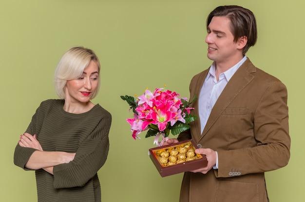 Jonge mooie paar gelukkige man die een doos met chocoladesuikergoed en een boeket bloemen geeft