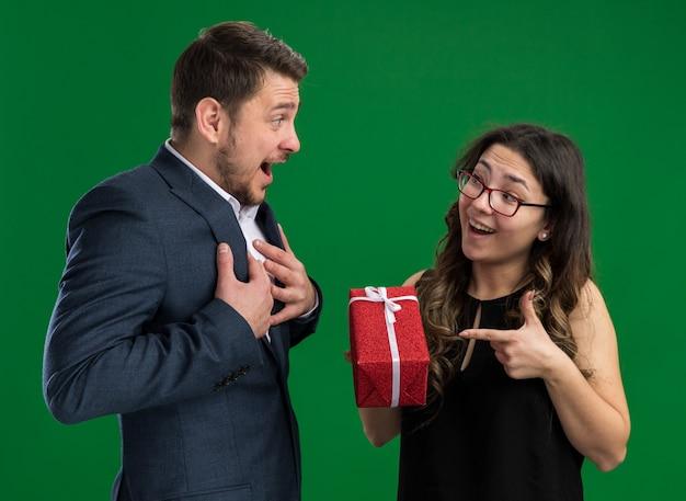 Jonge, mooie paar gelukkige man die een geschenk ontvangt van zijn vriendin die gelukkig verliefd is en samen valentijnsdag viert die over de groene muur staat