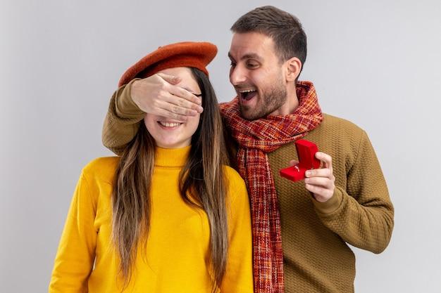 Jonge mooie paar gelukkige man die een voorstel doet met verlovingsring in rode doos aan zijn verbaasde vriendin in baret die haar ogen bedekt tijdens valentijnsdag staande over witte muur