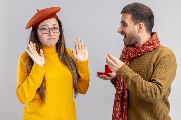 Jonge mooie paar gelukkige man die een voorstel doet met verlovingsring in rode doos aan zijn verwarde en ontevreden vriendin in baret tijdens valentijnsdag staande over witte muur