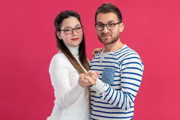 Jonge mooie paar gelukkige man en vrouw in vrijetijdskleding bril dansen gelukkig verliefd samen vieren valentijnsdag staande over roze muur