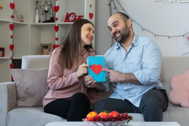 Jonge mooie paar gelukkige man en vrouw met boek tijd samen doorbrengen
