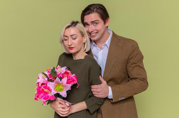 Jonge mooie paar gelukkige man en vrouw met boeket bloemen omarmen gelukkig verliefd samen glimlachend vieren internationale vrouwendag staande over groene muur