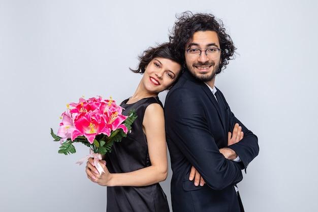 Jonge, mooie paar gelukkige man en vrouw met een boeket bloemen die er vrolijk en vrolijk lachend uitzien in liefde die valentijn viert