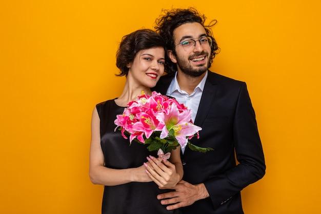 Jonge mooie paar gelukkige man en vrouw met een boeket bloemen glimlachend vrolijk omarmen gelukkig in de liefde