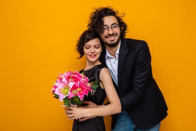 Jonge mooie paar gelukkige man en vrouw met een boeket bloemen glimlachend vrolijk omarmen gelukkig verliefd vieren valentijn love