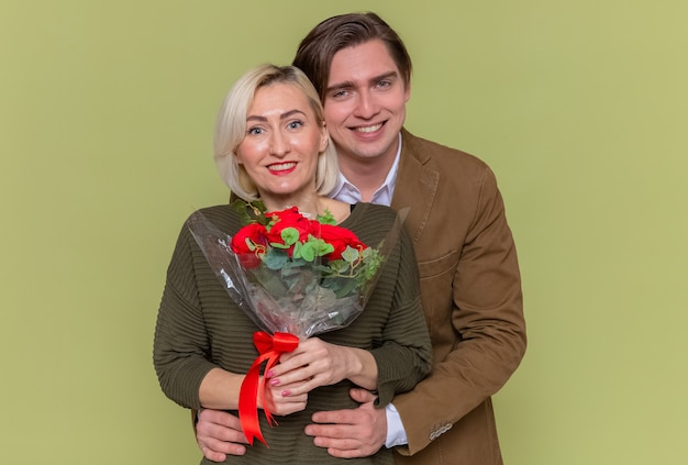 Jonge mooie paar gelukkige man met boeket van rode rozen en vrouw