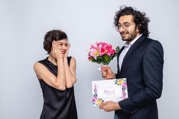 Jonge mooie paar gelukkige man met wenskaart die een boeket bloemen geeft aan zijn verraste en gelukkige vriendin die internationale vrouwendag op 8 maart viert