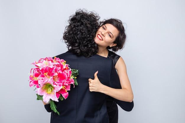 Jonge mooie paar gelukkige vrouw met boeket bloemen knuffelen haar vriendje duimen opdagen glimlachend
