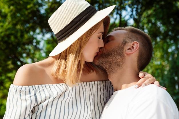 Jonge mooie paar glimlachen, kussen, omhelzen, wandelen in het park.