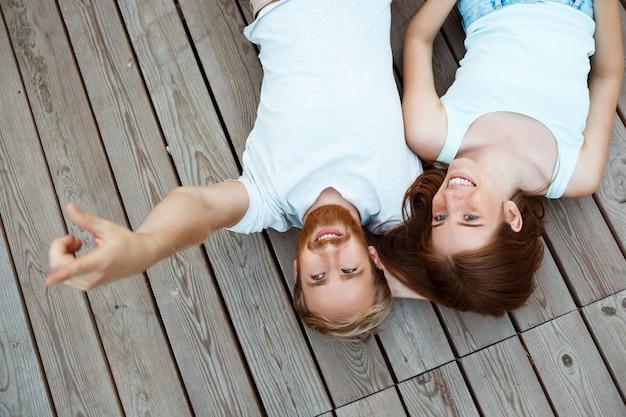 Jonge mooie paar glimlachen, liggend op houten planken