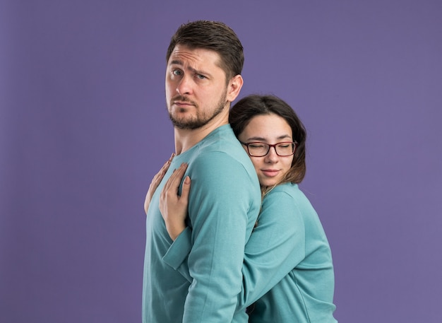 Jonge mooie paar in blauwe vrijetijdskleding gelukkige vrouw knuffelen haar vriendje gelukkig verliefd vieren valentijnsdag staande over paarse muur