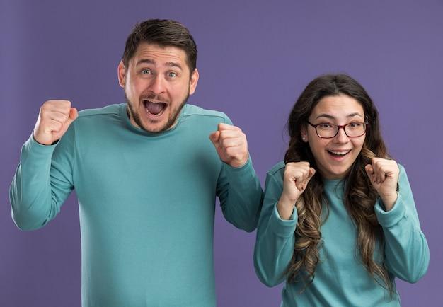 Jonge mooie paar in blauwe vrijetijdskleding man en vrouw balde vuisten gek blij en opgewonden staan over paarse muur