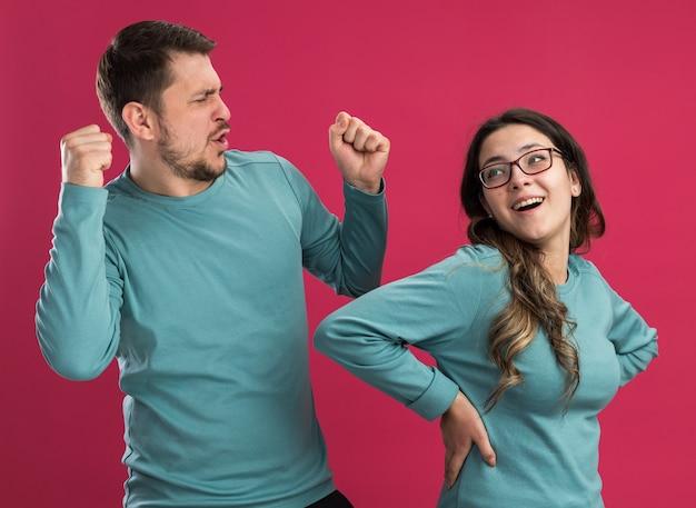 Jonge mooie paar in blauwe vrijetijdskleding man en vrouw blij en opgewonden plezier hebben samen gelukkig verliefd