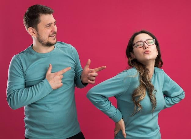 Jonge mooie paar in blauwe vrijetijdskleding man en vrouw gelukkig verliefd met plezier samen man wijzend op zijn mooie vriendin