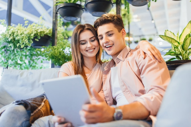 Jonge mooie paar in casual kleding op het zomerterras kijken naar de tablet