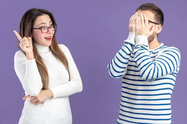 Jonge mooie paar in vrijetijdskleding blij en verbaasd vrouw kijken naar haar vriend die het gezicht bedekt met palmen valentijnsdag staande over paarse muur