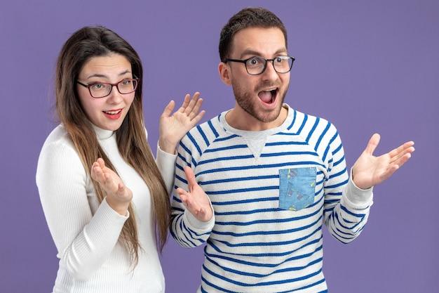 Jonge mooie paar in vrijetijdskleding blij en verrast man en vrouw kijken asidesmiling valentijnsdag concept staande over paarse muur