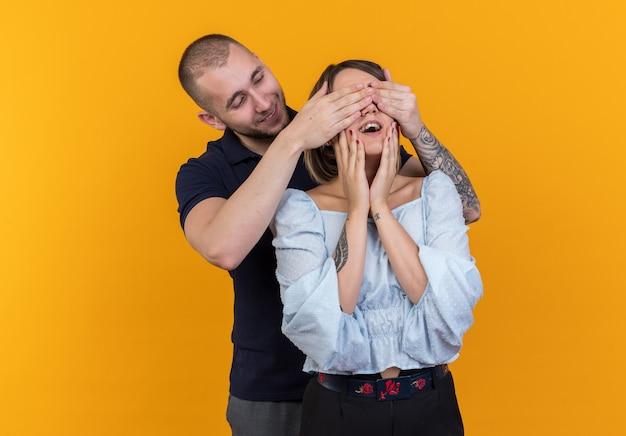Jonge, mooie paar in vrijetijdskleding, gelukkige man die achter zijn vriendin staat die haar ogen bedekt