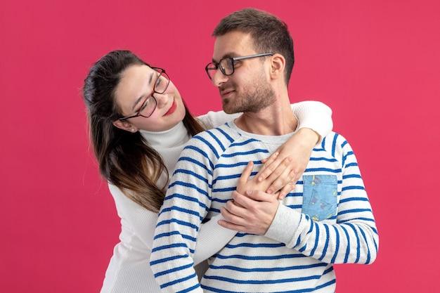 Jonge mooie paar in vrijetijdskleding gelukkige vrouw knuffelen haar glimlachende vriendje gelukkig verliefd samen vieren valentijnsdag staande over roze muur