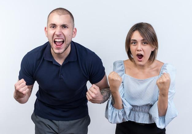 Jonge mooie paar in vrijetijdskleding man en vrouw balde vuisten blij en opgewonden op zoek staand