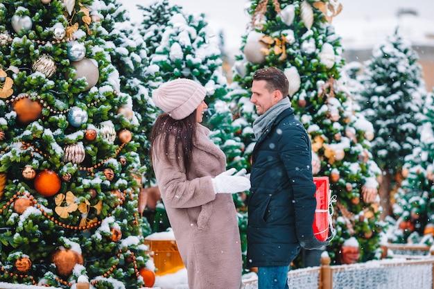 Jonge mooie paar kerstmis vieren in de stad straat en cadeau te geven aan elkaar