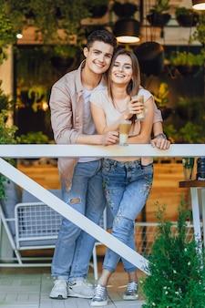 Jonge mooie paar knuffelen op het zomerterras van het restaurant in casual kleding met latte in hun handen