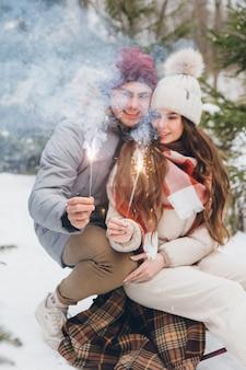 Jonge mooie paar knuffels en brandt sterretjes in een winter naaldbos zittend op een slee. een park met kerstbomen op de achtergrond. kerststemming. verven.