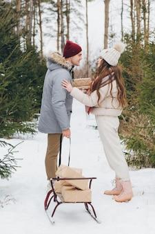 Jonge mooie paar knuffels en kusjes in een winter naaldbos en draagt dozen met geschenken op een slee. een park met kerstbomen op de achtergrond. kerststemming. verven.