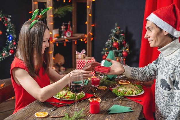 Jonge mooie paar liefhebbers brengen een feestelijk kerstdiner door
