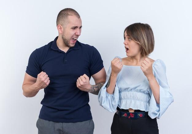 Jonge mooie paar man en vrouw blij en opgewonden gebalde vuisten permanent