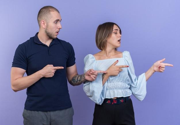 Jonge, mooie paar man en vrouw die opzij kijken, geïntrigeerd wijzend met wijsvingers naar de zijkant die over de blauwe muur staat