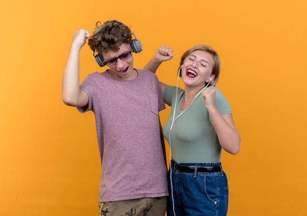 Jonge mooie paar man en vrouw, gekleed in vrijetijdskleding met koptelefoon blij en opgewonden genieten van favoriete muziek over oranje