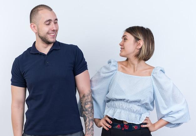 Jonge mooie paar man en vrouw gelukkig en positief kijken elkaar vrolijk glimlachend aan