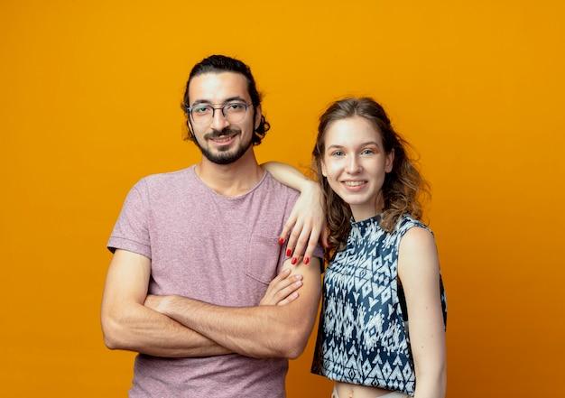 Jonge mooie paar man en vrouw gelukkig verliefd camera kijken permanent over oranje achtergrond