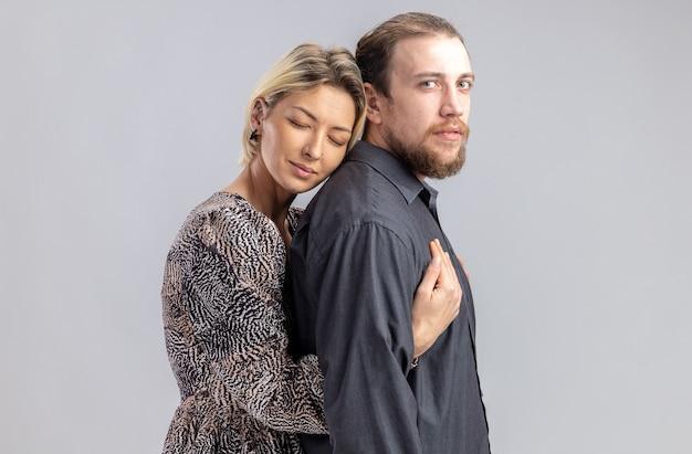 Jonge mooie paar man en vrouw gelukkig verliefd emracing vieren valentijnsdag staande over witte muur