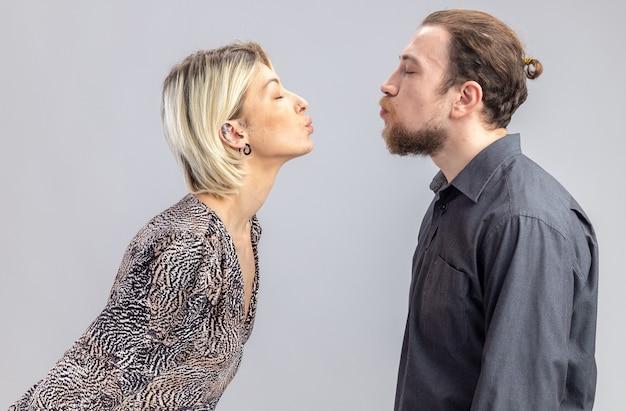Jonge mooie paar man en vrouw gelukkig verliefd gaan elkaar kussen vieren valentijnsdag staande over witte muur