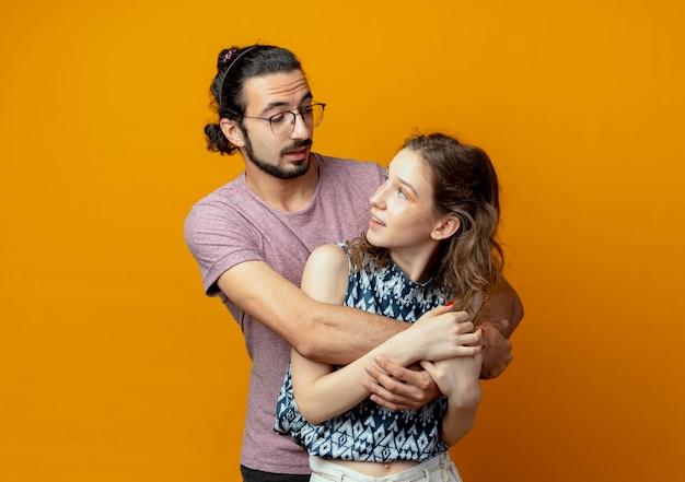 Jonge mooie paar man en vrouw gelukkig verliefd knuffelen samen staande over oranje muur