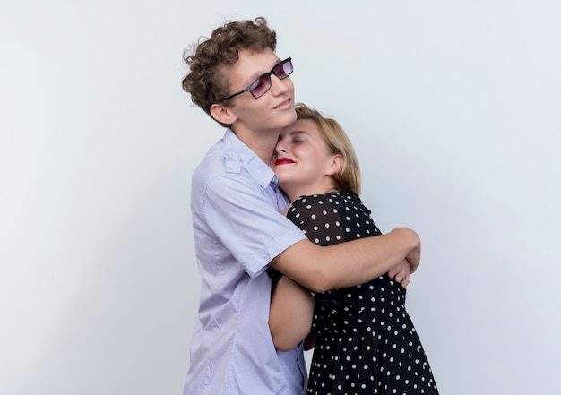 Jonge mooie paar man en vrouw gelukkig verliefd knuffelen staande over witte muur