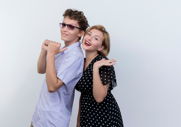 Jonge mooie paar man en vrouw gelukkig verliefd lachend over witte muur